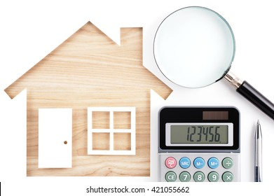 House shaped paper cutout, calculator, magnifier and pen on natural wood lumber. Isolated on white background.