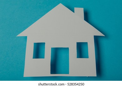 House shaped paper cutout on on blue background
