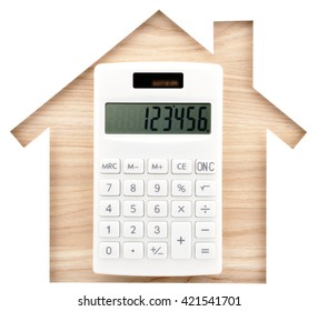 House shaped paper cutout and white calculator on natural wood lumber. Isolated on white background.