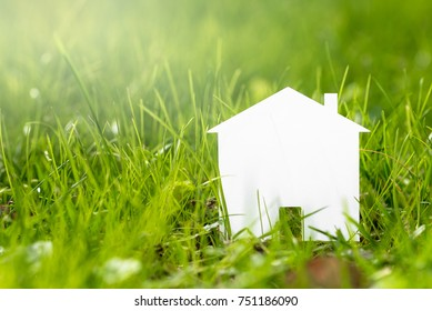 House Shaped Piece of Paper on a Grassy Field. Concept of Eco House.
