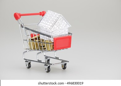 House in shopping cart with gold coins place on white background. Business and finance concepts rich and successful photography.