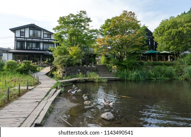 house, shops, and cafes along the kinrin lake reflecting in the calm lake water. Taken in Yufuin, Japan