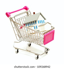 A house sits inside a shopping cart for real estate concepts.