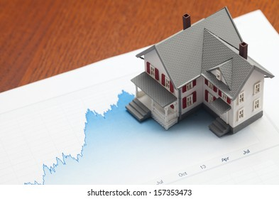 House sitting on graph. Concept of housing market.