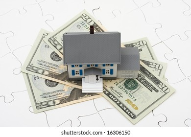 House sitting on money with puzzle. Understanding mortgages