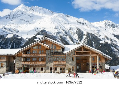 house in snow mountain and skiers