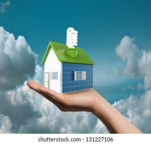 House with solar panels and lamp in hand