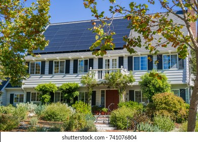 House with solar panels on the roof in a residential neighborhood of Oakland, in San Francisco bay on a sunny day, California
