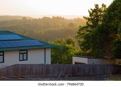 House with solar panels on roof in a mountain landscape at sunset. Wooden building with a background of mountainous forest at dusk. Heritage architecture and modern technology in Australia.