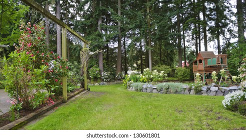 House spring backyard with roses patio and kids playground with wooden swing and slide.