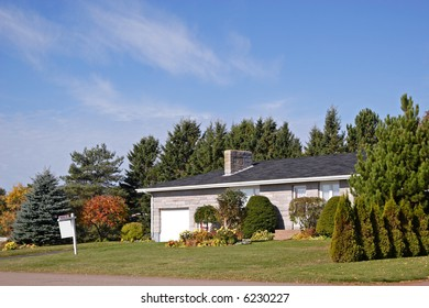 A house in the suburbs with a sold sign on the front lawn.