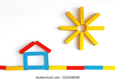 a house and the sun, both motifs laid with colored toy blocks