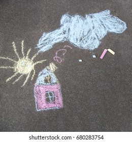 House and the sun - a children's drawing on the asphalt