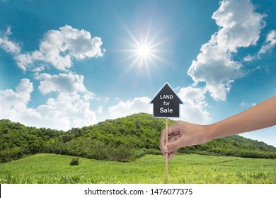 House symbol with location pin and Empty dry cracked swamp reclamation soil, land plot for housing construction project with and beautiful blue sky with fresh air Land for sales landscape concept