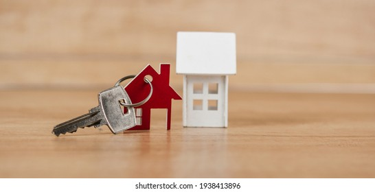 House symbol with metal key on wood table. Real estate, insurance concept, mortgage, buy sell house, realtor concept