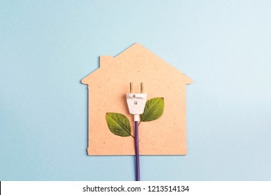 House symbol with plug like a plant on a blue  background. Save energy concept. Flat lay, top view.