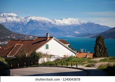 House with tiled roof near road at backraund of gorgeous nature, blue sea, snow peaks of mountains. Winter in Montenegro, Herceg Novi in the Bay of Kotor cold the Adriatic Sea.