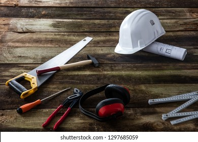 House tooling gear for building, maintenance, craftsmanship and repairing with hard hat, architect blue print, safety ear protection and many tools over wood background