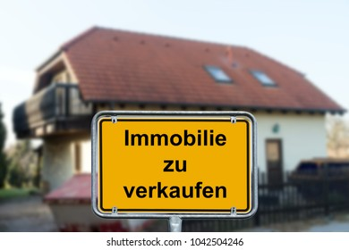 house and town sign with the german words real estate for sale