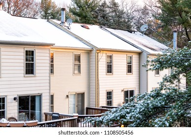 House townhomes rowhouses rooftop roof with chimneys covered in white winter snow, cold season in Virginia