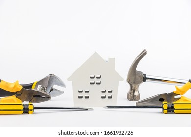 House toy and construction tools on white background with copy space.Real estate concept, New house concept, Finance loan business concept, Repair maintenance concept.