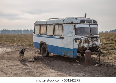 House trailer, made of rusty old Soviet bus, barking dog in Russian field on wastelands