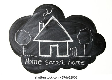 House and trees on cloud shaped blackboard with home sweet home message