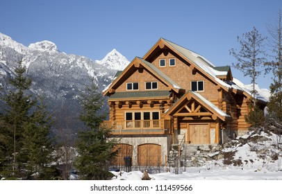 A house typical of west coast architechture, sits against the backdrop of the Tantalus Range in Squamish, British Columbia.