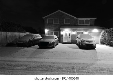 A house in the UK covered in light snow with CCTV and Security lights.