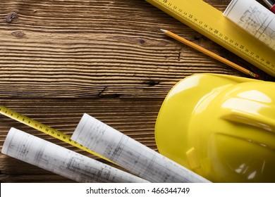 House under construction, blueprints and helmet, top view