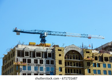 A house under construction and construction cranes on background of blue sky.