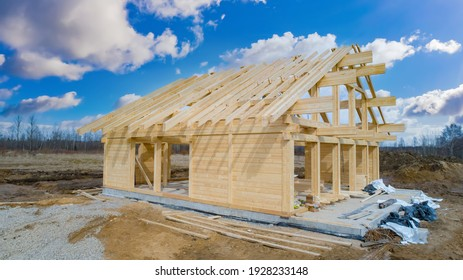 House under construction on sky background. Frame of a tree house. Concept - construction of frame houses. Erection of a cottage from wooden beams. Lumber for erection. Construction a country cottage
