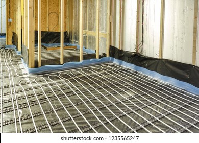 House under construction with underfloor heating water pipes installation to the subfloor