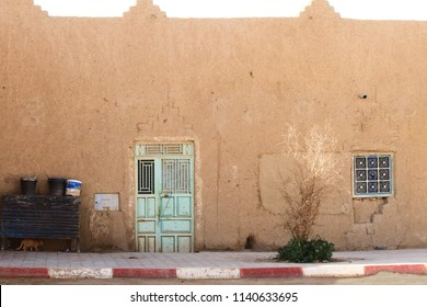 House in the village with cat and pistachio steel doors during sunny day on the outskirts of Sahara Desert. Morocco, Africa