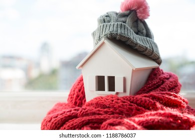 house in winter - heating system concept and cold snowy weather with model of a house wearing a knitted cap - Shutterstock ID 1188786037