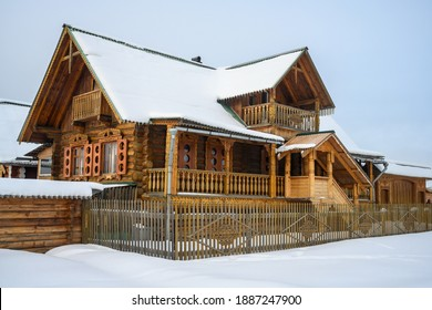 house in winter. rustic 2-storey house with wood carved facade elements, high porch, balcony, gate and fence. lifestyle in the Russian outback. clear winter day with white snow