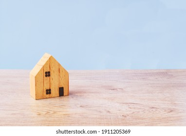 house wood model concept on table blue background and copy space for your investment insurance and home purchase mortgage real estate concept