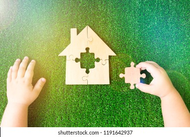 house of wooden puzzles, the child's hands, the missing element against the background of artificial green grass. real estate, insurance, investment planning.