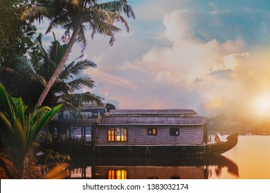 A houseboat is anchored in a lake at the Kerala Backwaters in India. The shot is taken during sunrise with the sun and beautiful cloudy sky in the background.