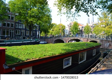 A houseboat in foreground. The canal, bridge and facades of houses in background. Amsterdam, The Netherlands.