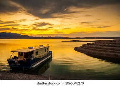 A houseboat moored to the muddy shores of the Lake Mead National Recreation Area, Nevada, at dusk with a dramatic and colorful cloudy sky - Holidays, tourism and vacation concept picture.