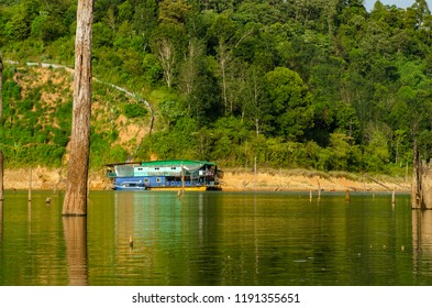Houseboat moored near the lakeshore under bright sunny day over beautiful nature background