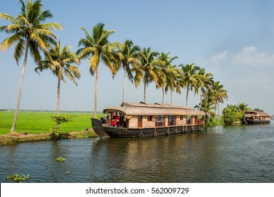 Houseboat traveling canals in Kerala India with palm trees lining waters edge