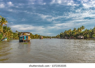 Houseboats in the backwater of alleppey  kerala showing the natural beauty of south india. Image taken from front angle showing backwater with palm trees and sky.