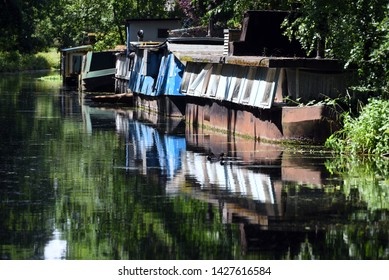 Houseboats reflected in the still waters of the beautiful Basingstoke Canal in Surrey