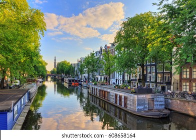 Houseboats at the UNESCO world heritage Prinsengracht canal with the Westerkerk (Western church) on a summer morning with a blue sky and clouds and a mirror reflection in Amsterdam, The Netherlands