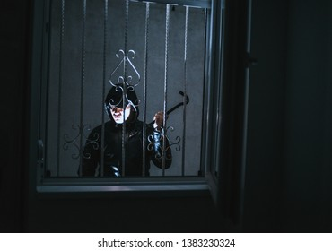 Housebreaker with crowbar tool trying to get in the house to rob it