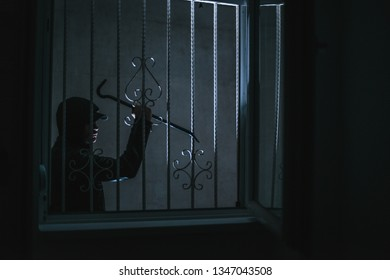 Housebreaker standing next to the window and prepares to break in the apartment