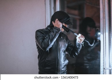Housebreaker wearing black clothes and leather coat breaking in a house