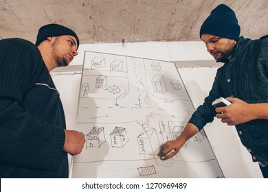 Housebreakers standing near the map and planning a crime